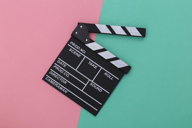 Доска трещотки кино на сине-розовом пастельном фоне. кинопроизводство, кинопроизводство, индустрия развлечений. вид сверху