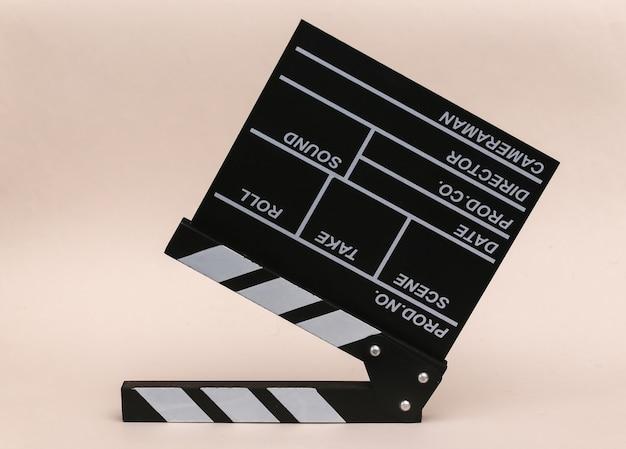 Доска трещотки кино на бежевом фоне. киноиндустрия, развлечения