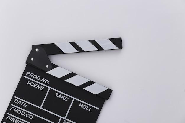 Доска трещотки кино на белой предпосылке. кинопроизводство, кинопроизводство, индустрия развлечений. вид сверху