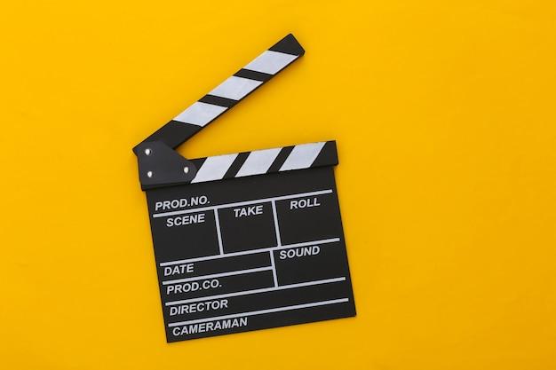 Доска трещотки кино на желтом фоне. кинопроизводство, кинопроизводство, индустрия развлечений. вид сверху