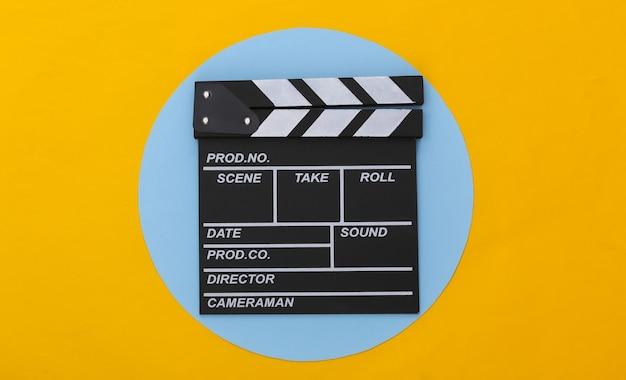 Доска трещотки кино на желтом синем фоне. кинопроизводство, кинопроизводство, индустрия развлечений. вид сверху
