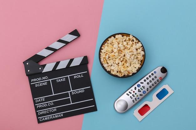 映画のカチンコ、ポップコーンボウル、3dメガネ、ピンクブルーの背景にテレビのリモコン。エンターテインメント業界。上面図。フラットレイ