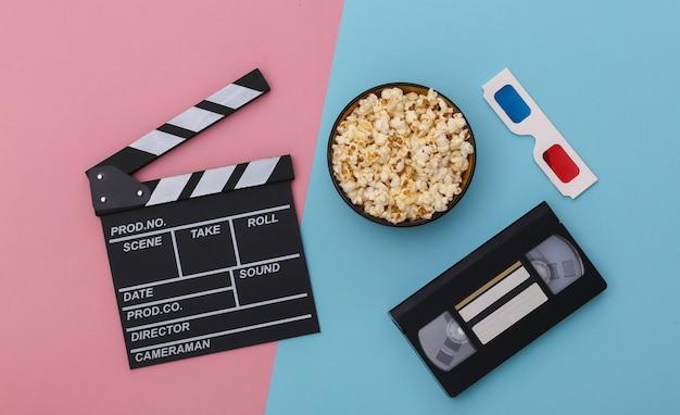 映画のカチンコ、ポップコーンボウル、3dメガネ、ピンクブルーの背景にビデオカセット。エンターテインメント業界。上面図。フラットレイ