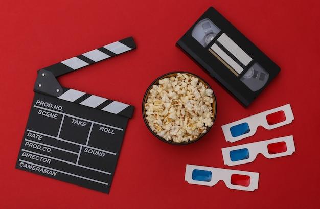 映画のカチンコ、ポップコーンボウル、3dメガネ、赤い背景のビデオカセット。エンターテインメント業界。上面図。フラットレイ