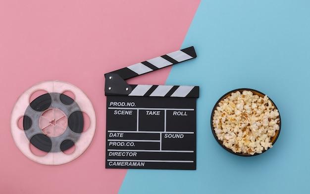 ピンクブルーの背景に映画のカチンコ、ポップコーンボウル、フィルムリール。エンターテインメント業界。上面図。フラットレイ
