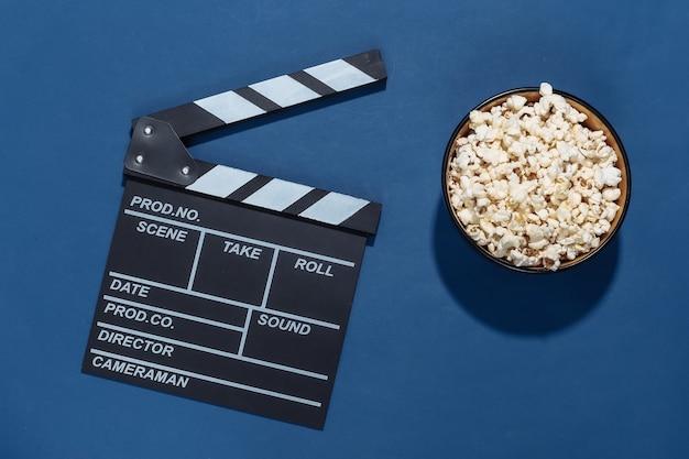 映画のカチンコ、深い影のある古典的な青い背景のポップコーンボウル。エンターテインメント業界。上面図