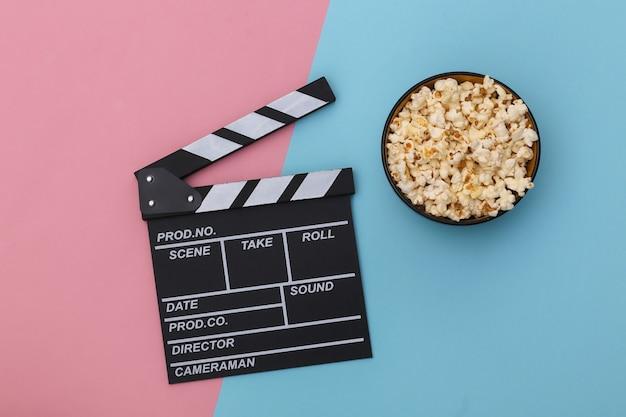 映画のカチンコ、ピンクブルーの背景にポップコーンボウル。エンターテインメント業界。上面図。フラットレイ
