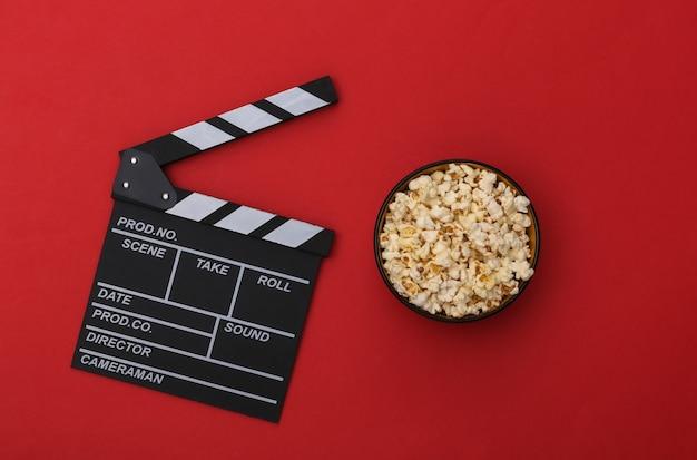 映画のカチンコ、赤い背景のポップコーンボウル。エンターテインメント業界。上面図。フラットレイ