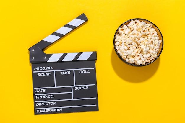 映画のカチンコ、深い影のある黄色の背景にポップコーンボウル。エンターテインメント業界。上面図