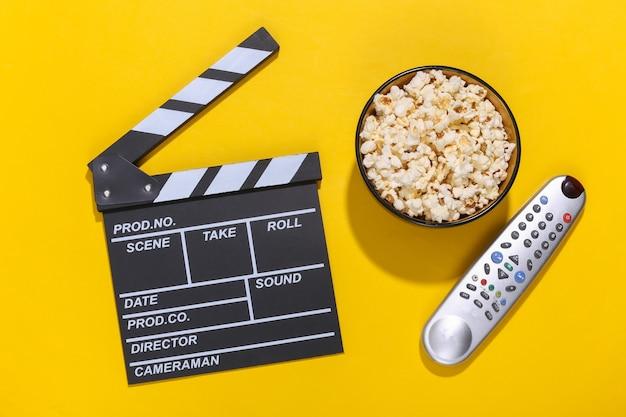 映画のカチンコ、ポップコーンボウル、深い影のある黄色の背景のテレビのリモコン。エンターテインメント業界。上面図