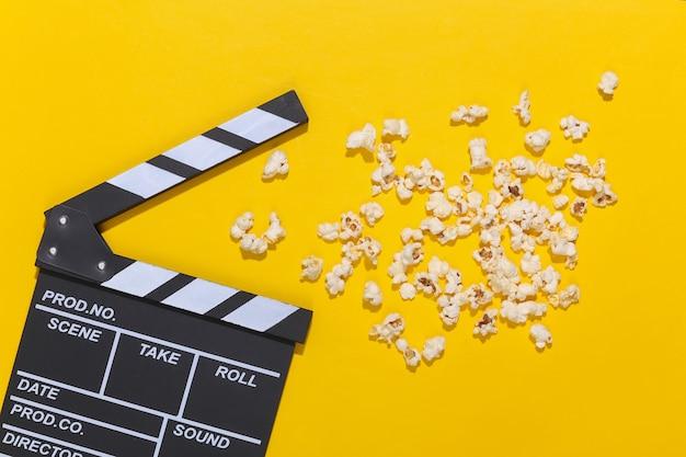 映画のカチンコ、深い影のある黄色の背景にポップコーン。エンターテインメント業界。上面図