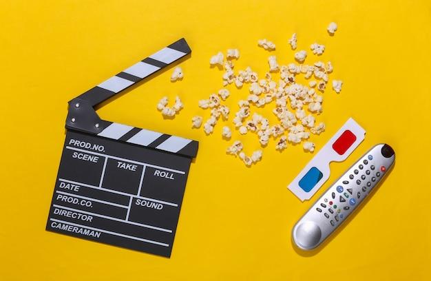 映画のカチンコ、ポップコーン、テレビのリモコン、深い影のある黄色の背景の3dメガネ。エンターテインメント業界。上面図