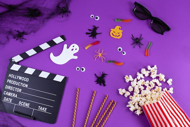 Movie clapper board in spider webs spiders ghost eyes on purple lilac background