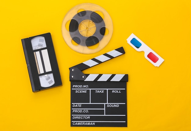 Movie clapper board, video cassette and film reel, 3d glasses on yellow background. cinema industry, entertainment. top view