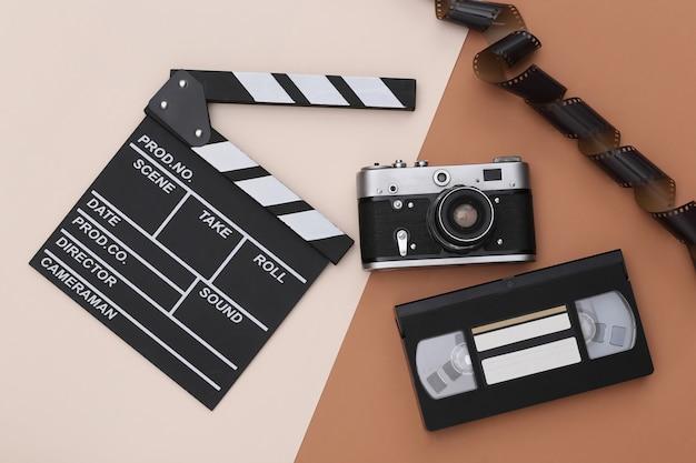 Доска с хлопушкой фильма, видеокассета, пленка, фотоаппарат на бежевом коричневом фоне. кинопроизводство, кинопроизводство, индустрия развлечений. вид сверху