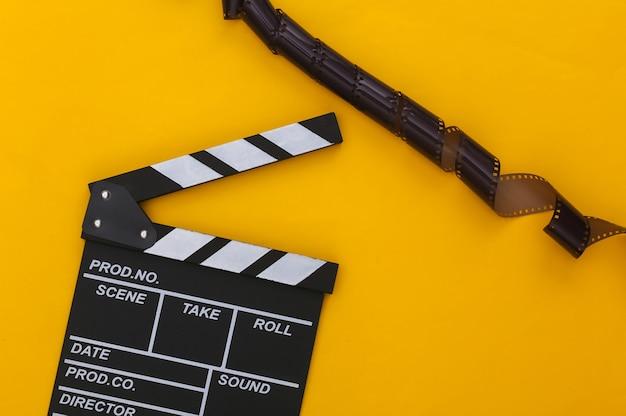 Доска с хлопушкой фильма с пленкой на желтом фоне. кинопроизводство, кинопроизводство, индустрия развлечений. вид сверху