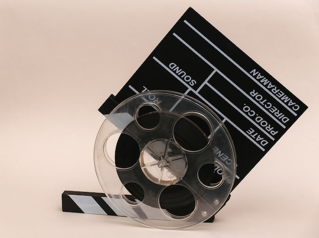 Movie clapper board with film reel on beige background. cinema industry, entertainment