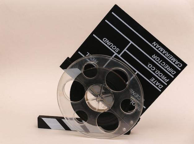 Доска с хлопушкой фильма с катушкой пленки на бежевом фоне. киноиндустрия, развлечения