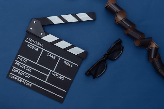 필름 테이프가 있는 영화 클래퍼 보드, 고전적인 파란색 배경에 3d 안경. 영화 제작, 영화 제작, 엔터테인먼트 산업. 컬러 2020. 탑 뷰