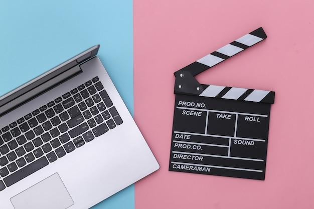 Доска с хлопушкой фильма с ноутбуком на сине-розовом пастельном фоне. кинопроизводство, кинопроизводство, индустрия развлечений. вид сверху