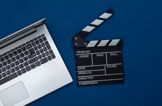 Доска с трещоткой кино с ноутбуком на классическом синем фоне. кинопроизводство, кинопроизводство, интернет-кинотеатр. вид сверху