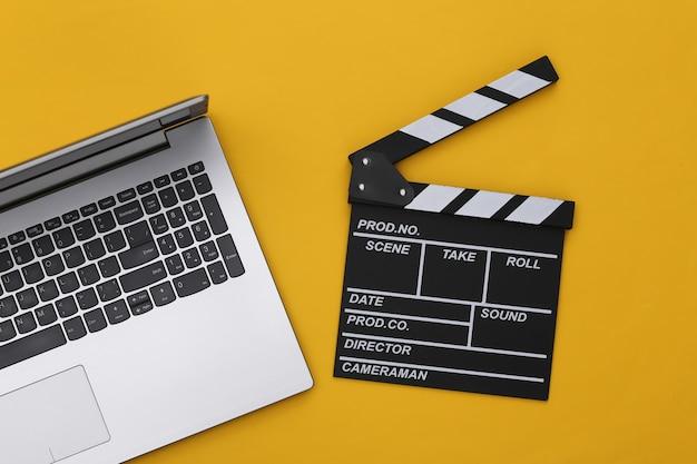노란색 배경에 노트북이 있는 영화 클래퍼 보드. 영화 제작, 영화 제작, 온라인 영화. 평면도
