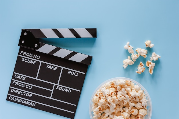 Movie clapper board with popcorn on blue background for entertainment