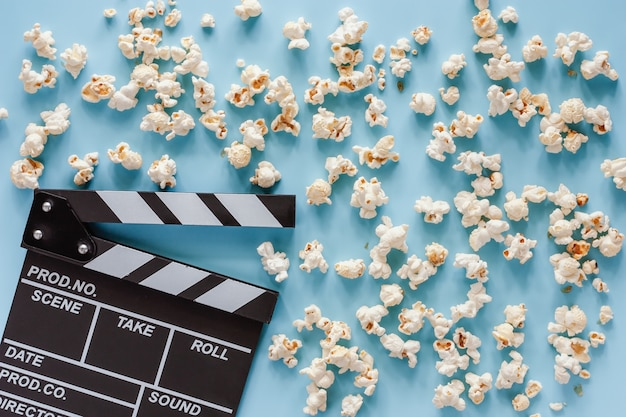Movie clapper board with popcorn on blue for entertainment concept