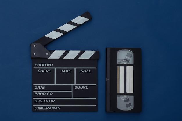 Доска с хлопушкой фильма с видеокассетой на классическом синем фоне. кинопроизводство, кинопроизводство, индустрия развлечений. цвет 2020. вид сверху