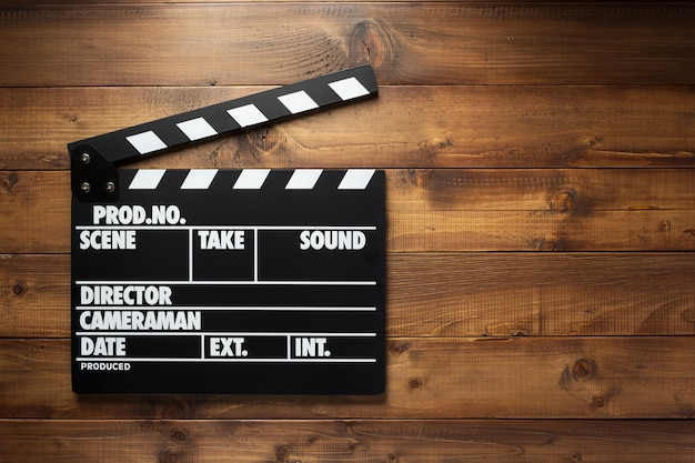 Movie clapper board at wooden background texture, top view