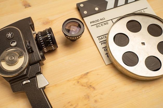 映画クラッパー、フィルム リール、木製のテーブルの上のカメラ、トップ ビュー