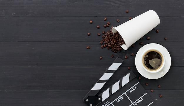 映画のクラッパー、ホットコーヒー、黒い木の豆