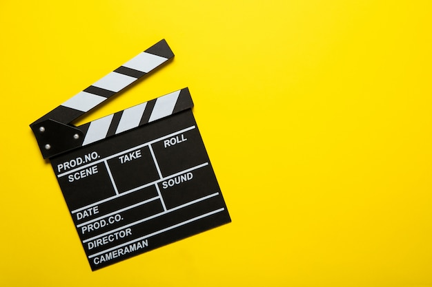 Фильм клаппер на желтом фоне, вид сверху. место для текста