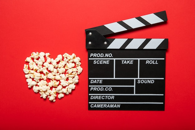 Movie clapper and popcorn on a red background