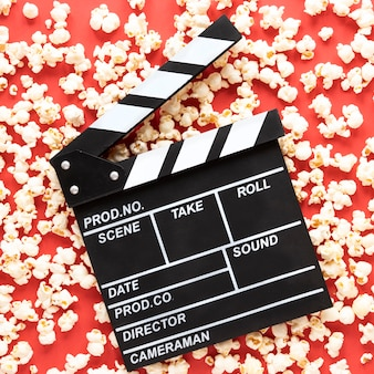 Movie clapper on red background with popcorn all around