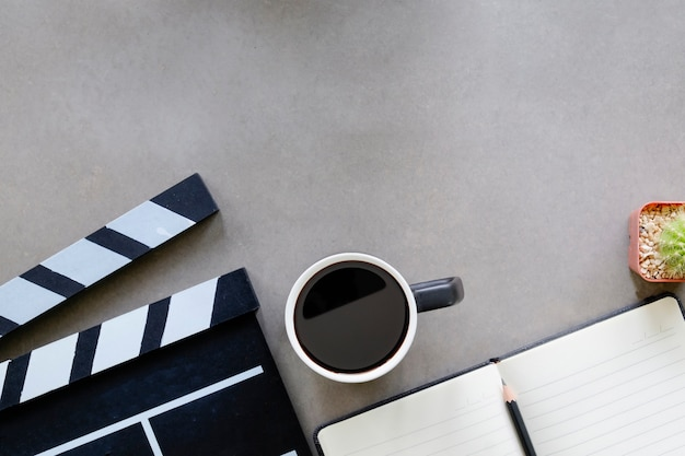 Кино клаппер с блокнотом бумаги, чашку кофе, кактус на столе вид сверху директор и копией пространства.