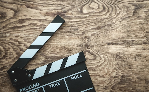 Movie clapper on wooden background.