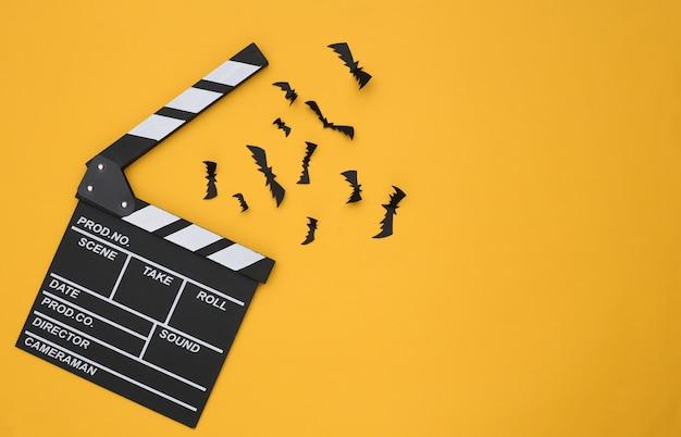 영화 clapperboard와 노란색 배경에 박쥐입니다. 할로윈 공포 영화. 평면도