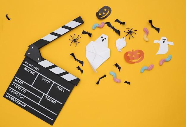 영화 클래퍼보드와 수제 할로윈 종이 장식, 노란색 배경에 거미 벌레. 평면도