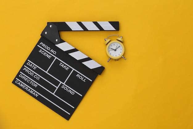 黄色の背景に映画のカチンコとミニ目覚まし時計。