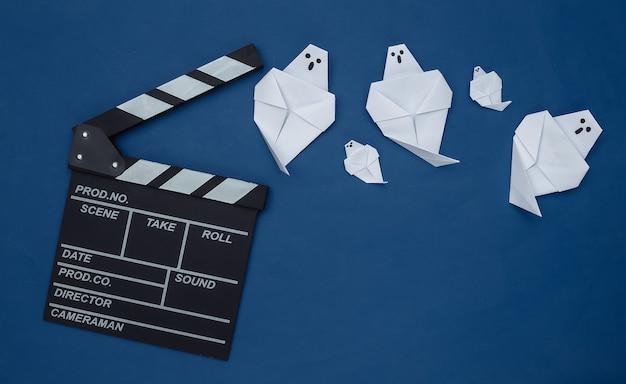 고전적인 파란색 배경에 영화 클래퍼보드와 종이 유령. 할로윈 공포 영화. 평면도