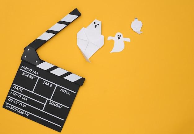 노란색 배경에 영화 clapperboard 및 종이 유령. 할로윈 공포 영화. 평면도