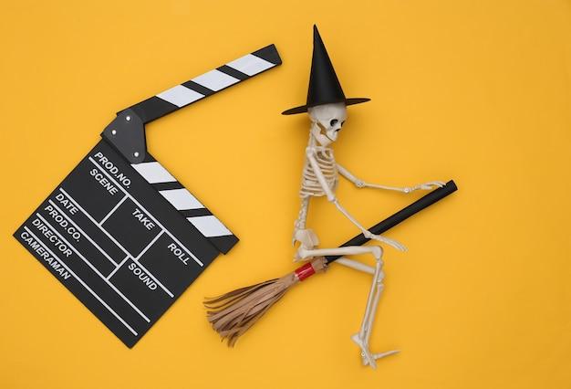노란색 배경에 빗자루가 달린 마녀 모자를 쓴 영화 클래퍼보드와 해골. 할로윈 공포 영화. 평면도