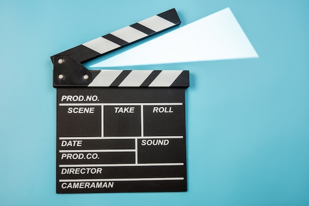 Movie clapperboard on blue background