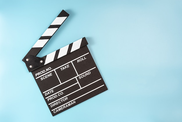 Movie clapperboard on blue space