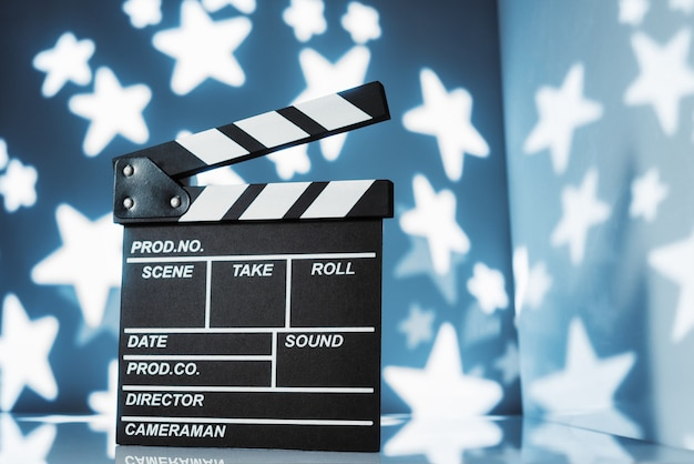 Movie clapperboard on blue starry space