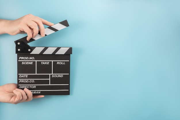 Movie clapperboard in hands on a blue space