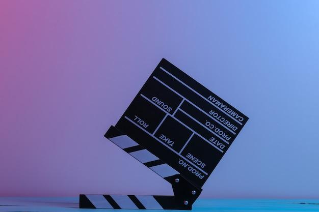 빨간색 파란색 네온 불빛에 영화 clapperboard입니다. 연예 사업