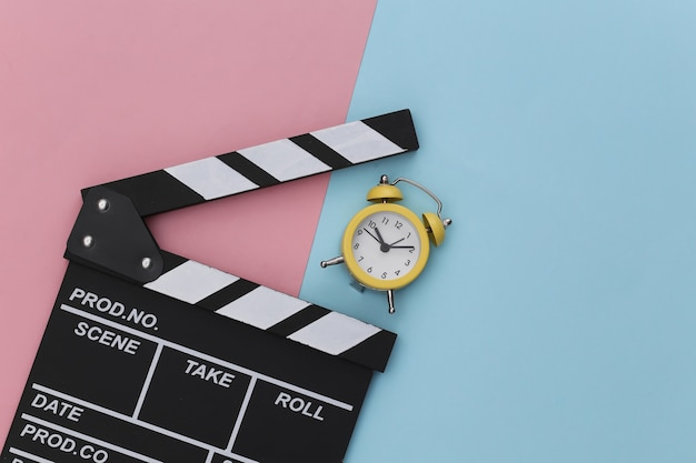 Movie clapperboard and mini alarm clock on a blue-pink pastel background.