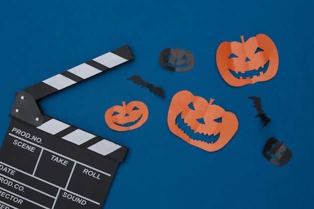 영화 클래퍼보드, 종이는 고전적인 파란색 배경에 날아다니는 박쥐와 할로윈 호박을 잘라냅니다. 할로윈 공포 영화. 평면도